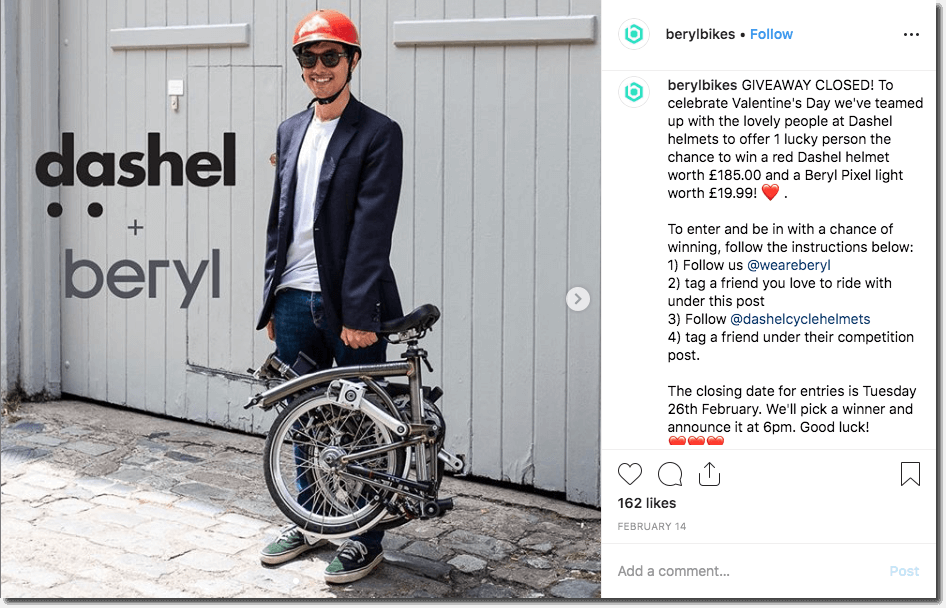 Screenshot of an Instagram giveaway by a cycling brand. The main image shows a casually-dressed young man, wearing a red helmet and sunglasses, and carrying a folding bike in one hand. The competition invites people to follow, comment, and tag for the chance to win a helmet and lights.