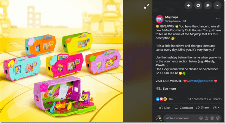 Screenshot of a Facebook post from toy brand MojiPops. The main image shows a set of 6 toys. The caption asks users to pick which figure is the answer to a riddle, and describe why they would like to win the set of 6 toys.