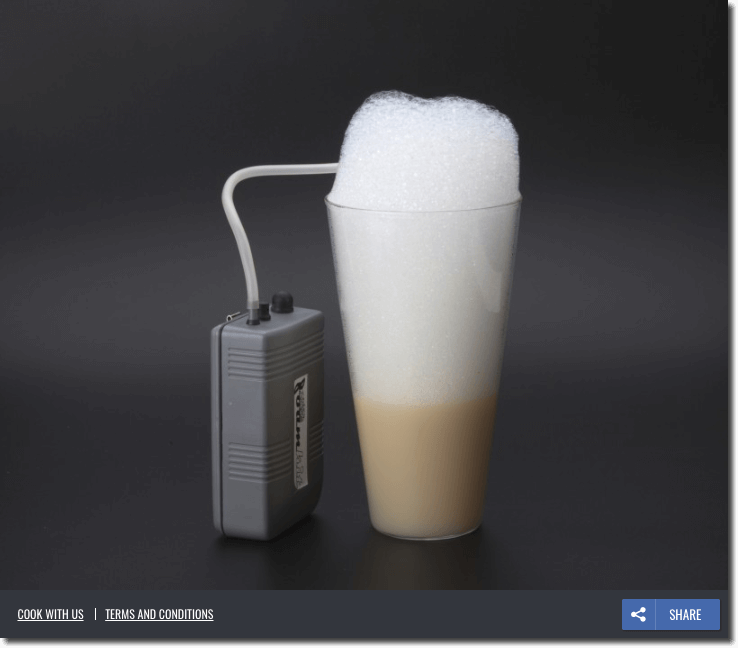 "The image shows a foaming tool: a grey box with a rubber pipe leading into a glass of coffee, which is filled to overflowing with foam. The background is a deep, minimalist grey. The only text is 3 small buttons at the bottom of the image: ""cook with us"", ""terms and conditions"", and ""share""."