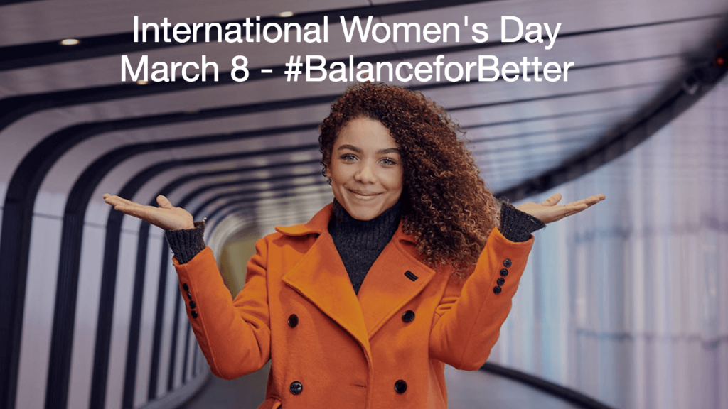 """Screenshot of a banner announcing the International Women's Day photo competition. The image shows a woman holding up her hands in the """"Balance for Better"""" pose. The image is titled """"International Women's Day, March 8 - Balance for Better"""""""