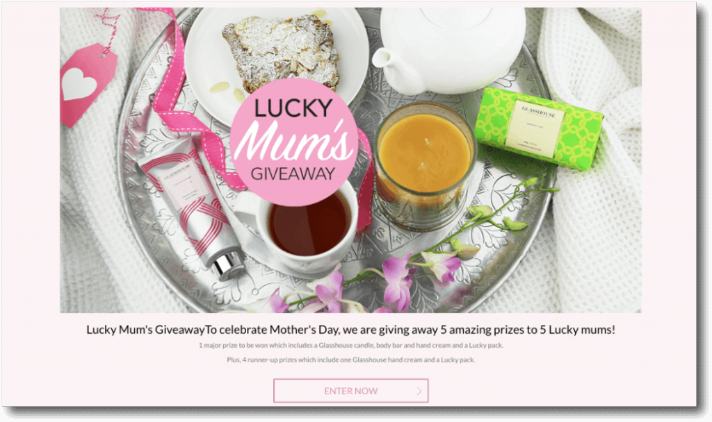 "Banner announcing a Mother's Day giveaway. The image shows a breakfast tray with tea, candles, cake, a teapot, and luxury toiletries. The text below reads: ""Lucky Mums Giveaway. To celebrate Mother's Day, we are giving away 5 amazing prizes to 5 lucky mums!"""
